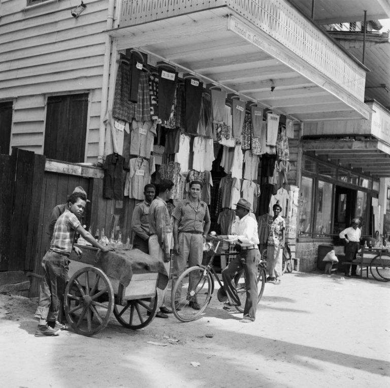 OUDE FOTO 47 Een kledingwinkel in de Maagdenstraat in Paramaribo. Op de voorgrond een jongen met een drankkarretje