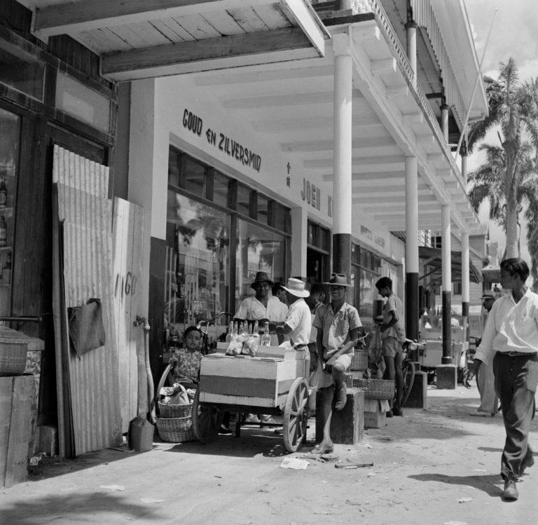 OUDE FOTO 49 Een kledingwinkel in de Maagdenstraat in Paramaribo. Op de voorgrond een jongen met een drankkarretje